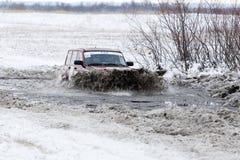 El coche de la reunión 4WD supera una charca mitad-congelada Foto de archivo