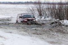 El coche de la reunión 4WD supera una charca mitad-congelada Imágenes de archivo libres de regalías
