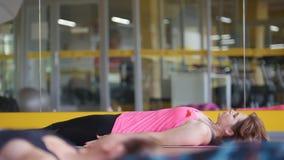 El coche de la yoga realiza los ejercicios para la flexibilidad - grupo de mujeres en el gimnasio - telephoto almacen de metraje de vídeo