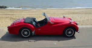 El coche de tragante abierto clásico de deportes del rojo MGA parqueó en la 'promenade' de la orilla del mar Imágenes de archivo libres de regalías