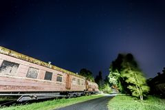 El coche de tren viejo oxidado con alguno protagoniza en el cielo Foto de archivo libre de regalías
