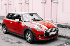 El coche del color rojo con blanco raya a Mini Cooper Parked On Street adentro imagen de archivo libre de regalías