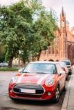 El coche del color rojo con blanco raya a Mini Cooper Parked On Street encendido fotografía de archivo libre de regalías