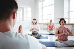 El coche del hombre entrena al grupo de ejercicios de la yoga de las mujeres para la atención sanitaria que mantiene en la clase  foto de archivo