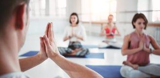 El coche del hombre entrena al grupo de ejercicios de la yoga de las mujeres para la atención sanitaria que mantiene en la clase  imágenes de archivo libres de regalías