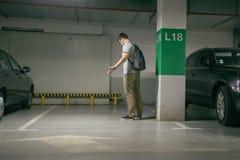 El coche del ` s del hombre fue robado, puede coche del hallazgo del ` t en el estacionamiento subterráneo foto de archivo