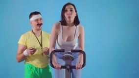 El coche divertido del hombre a partir de años 80 con el bigote y los vidrios examina a una mujer joven en la bicicleta estática metrajes