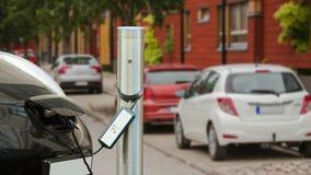 El coche eléctrico se carga en el estacionamiento cerca de la casa metrajes