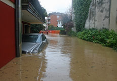 El coche en el patio de la casa se sumergió por el fango de la inundación Fotos de archivo