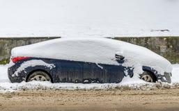 El coche en la calle está nevado en invierno Foto de archivo