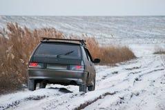 El coche en un camino de tierra del invierno Foto de archivo