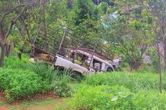 El coche es oxidado y roto en el campo verde en la hierba con la luz hermosa de la mañana - imagen imagenes de archivo