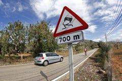 El coche está alcanzando a un ciclista en un camino con muchas curvas foto de archivo libre de regalías