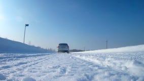 El coche está conduciendo en un camino del invierno sobre la cámara almacen de metraje de vídeo