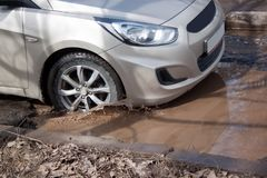 El coche está conduciendo el thtough que un agujero grande llenó de agua Capa de balasto destruida peligrosa imagen de archivo