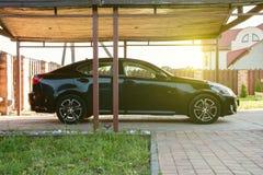 El coche está debajo de un toldo, un garaje abierto, el territorio de la voluntad de la casa foto de archivo libre de regalías