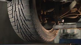 El coche está levantando en el soporte del servicio del vehículo, servicio de reparación del coche, alineación de rueda, coche qu almacen de video