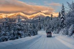 El coche está montando en el camino de la nieve del polvo en las montañas Imagen de archivo libre de regalías
