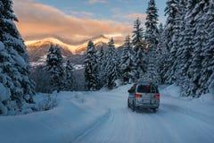 El coche está montando en el camino de la nieve del polvo en las montañas Imagenes de archivo