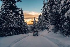 El coche está montando en el camino de la nieve del polvo en las montañas Foto de archivo