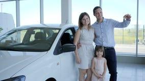 El coche familiar, familia feliz del retrato que compra el nuevo auto, llaves del automóvil en la mano del ` s del cliente, gente metrajes