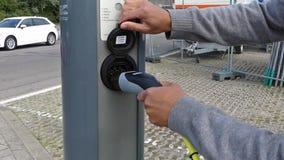 El coche híbrido eléctrico tapa en la estación de carga almacen de metraje de vídeo