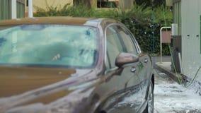 El coche hermoso sale del túnel de lavado costoso, automóvil limpio, buen servicio auto almacen de metraje de vídeo