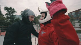 El coche masculino da instrucciones a una muchacha del skydiver antes de volar en el túnel de viento almacen de metraje de vídeo