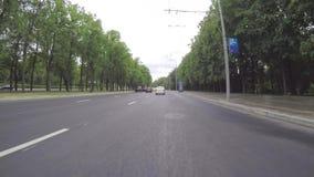El coche monta en la calle de la ciudad, que corre a través del parque Primera opinión de la persona de la carrocería metrajes