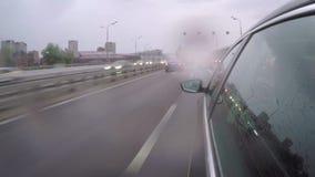 El coche monta en la carretera durante hora punta bajo la lluvia Vista lateral de la carrocería metrajes