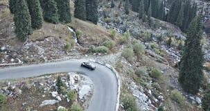 El coche monta en la carretera en las montañas Tiroteo del abejón del top y del lado almacen de metraje de vídeo