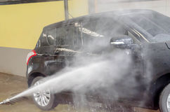 El coche negro que se lava por el arma de la lavadora de la presión en túnel de lavado hace compras Imagenes de archivo
