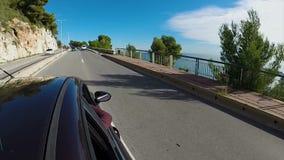 El coche negro que va abajo de la carretera costera, manos de pasajeros se pega fuera de ventana almacen de video