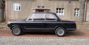 El coche negro viejo del vintage parqueó delante de una casa Fotos de archivo
