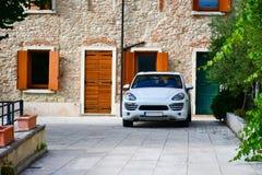 el coche parqueó delante de la casa de piedra en San Zeno di Montagna, Italia fotografía de archivo libre de regalías