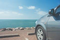 El coche parqueó en estacionamiento en la costa cerca de la playa con paisaje marino y del cielo azul en el fondo fotografía de archivo