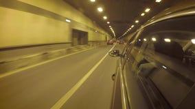 El coche pasa a través del túnel en la circulación densa Vista lateral de la carrocería metrajes