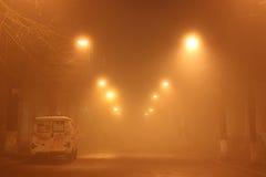 El coche quebrado permanece abajo de la carretera en la niebla del invierno Foto de archivo