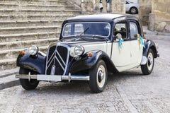 El coche retro del fondo aguarda a los recienes casados en la entrada a la iglesia en Jerez de la Front Imagen de archivo libre de regalías