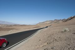 El coche rojo corre en el camino del desierto con las montañas en horizonte fotos de archivo libres de regalías