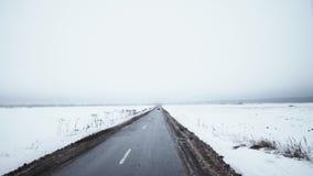 El coche rojo del músculo comienza a conducir en el camino rodeado por los campos cubiertos en nieve almacen de video