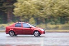 El coche rojo está conduciendo en un camino mojado Imagen de archivo libre de regalías