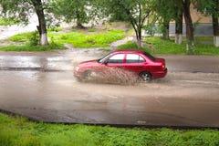 El coche rojo va en el camino de ciudad a un mán tiempo Imagenes de archivo