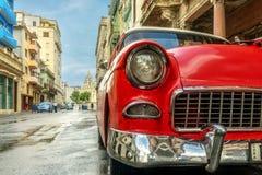 El coche rojo viejo se está colocando en una calle vieja con los charcos después de un su Fotos de archivo