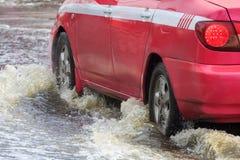 El coche salpica a través de un charco grande en inundado imagen de archivo