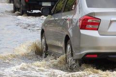 El coche salpica a través de un charco grande en inundado fotografía de archivo libre de regalías