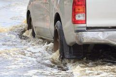 El coche salpica a través de un charco grande en inundado imágenes de archivo libres de regalías