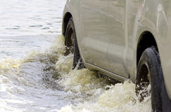El coche salpica a través de un charco grande en una calle inundada fotos de archivo libres de regalías