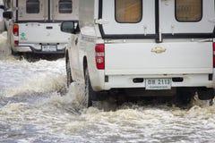 El coche salpica a través de un charco grande en una calle inundada fotos de archivo