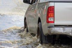 El coche salpica a través de un charco grande en una calle inundada imagen de archivo libre de regalías